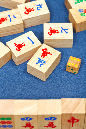 wooden tiles in mahjong game durung playing on blue cloth table close up photo