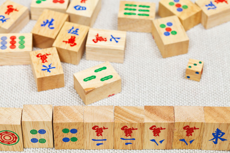 wooden tiles in mahjong game durung playing on textile table close up photo
