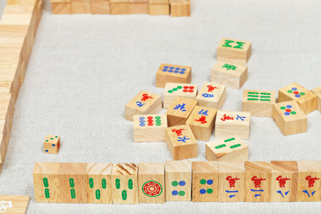 player hand from wooden tiles in mahjong game on textile table photo