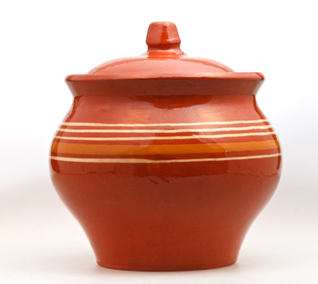 side view of closed earthenware pot on white background photo