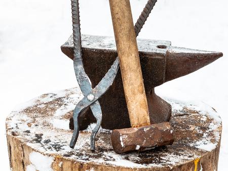 smithy: incudine con il martello fabbro e tenaglie vecchia fucina di fondo in inverno