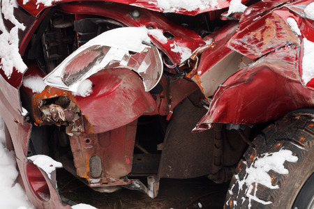 headlamp: broken headlamp and crumpled hood of red car after winter traffic accident