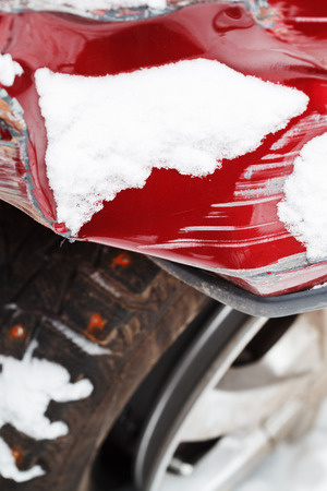 bonnet up: crumpled fender of red car after winter traffic accident Stock Photo
