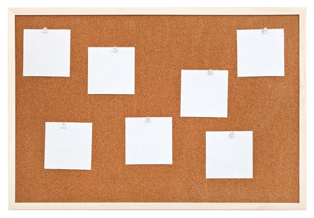 several sheets of paper on bulletin cork board isolated on white background photo