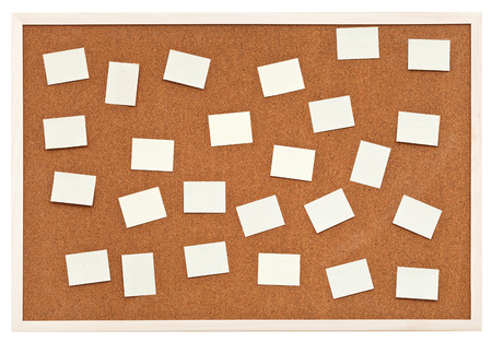 many small sheets of paper on bulletin cork board isolated on white background photo