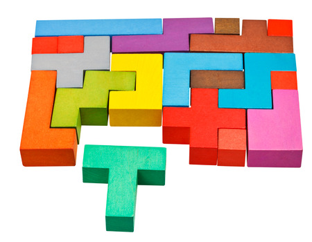 multicoloured puzzle blocks and T-shaped piece isolated on white background photo