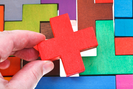 putting cross shaped block in wooden multicoloured puzzle isolated on white background photo