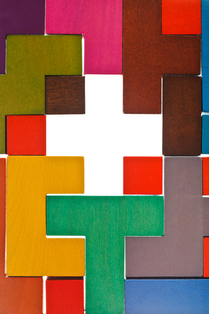 top view of cross shape hole in wooden multicoloured puzzle photo
