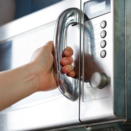 Apertura della porta del forno a microonde in cucina di casa Archivio Fotografico - 25917939