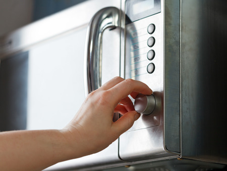 mujeres cocinando: encender el horno de microondas en la cocina de casa