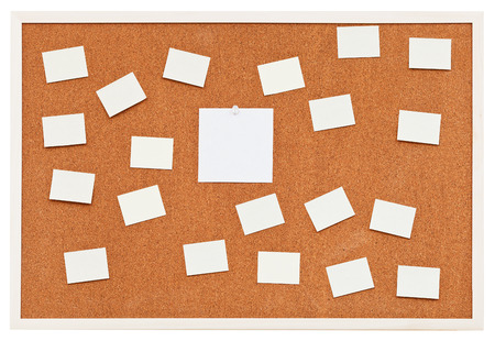 small sheets of paper on bulletin cork board isolated on white background photo