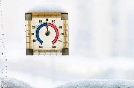 thawing: zero degrees on home window thermometer in thawing winter day Stock Photo