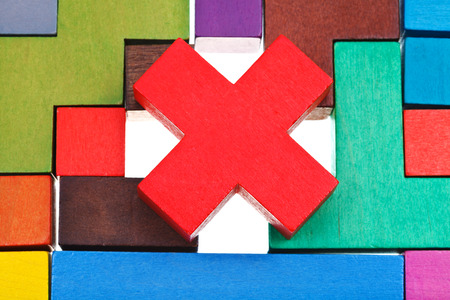 cross shaped block on wooden multicoloured puzzle isolated on white background photo