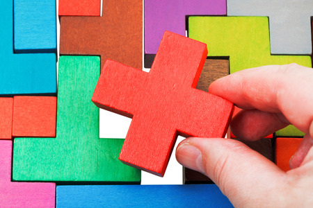 putting cross shaped piece in wooden multicoloured puzzle isolated on white background photo
