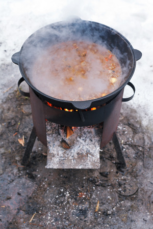 food stewed in cauldron on mobile brazier outdoors in winter photo