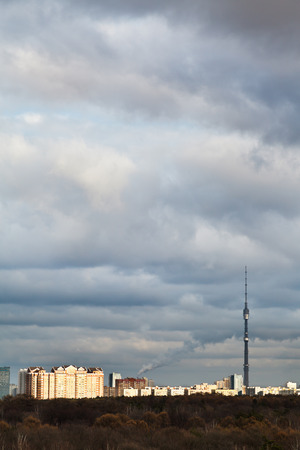 grey blue evening clouds over urban houses and TV tower on sunset photo