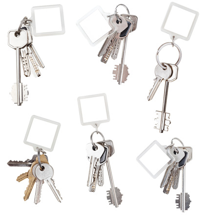 trinket: collection of bunch of home keys with blank square keychain isolated on white background