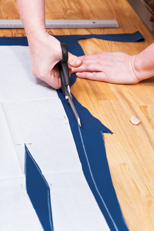 dressmaking clothes from blue fabric according with pattern photo