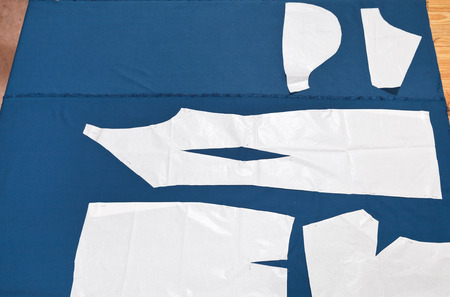 out of production: paper model of apparel on blue fabric for dress cutting