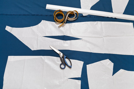 tailor tools and paper sample of clothes on blue fabric for dress cutting photo