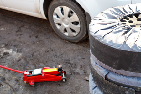 lifting jack: seasonal replacement of car tires with jack outdoors - preparation for repair