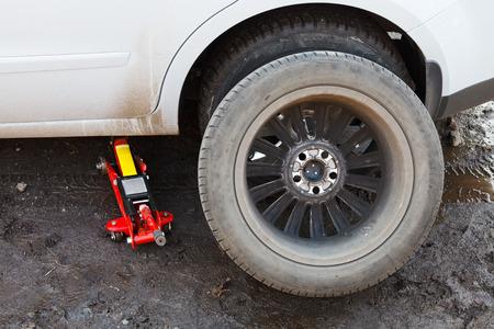 seasonal replacement of car tires with jack outdoors - preparing wheel
