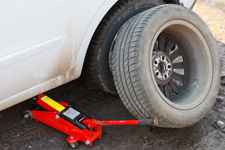 tire fitting: seasonal replacement of tires with jack outdoors - lifting car by hydraulic jack Stock Photo