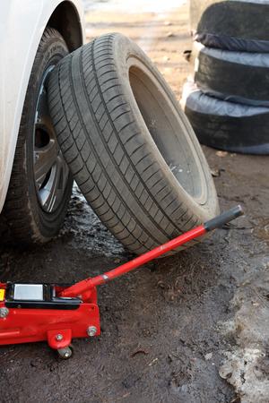 tire fitting: seasonal replacement of tires with jack outdoors - car tire fitting