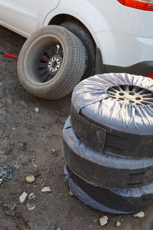 seasonal replacement of tires with jack outdoors - choice of wheel photo