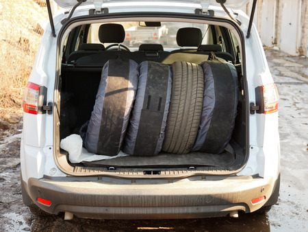 tire fitting: seasonal tire replacement - set of tires in trunk of car
