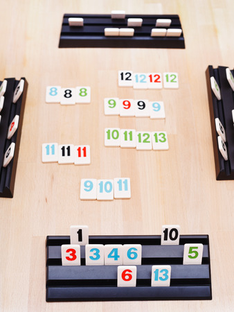 MOSCOW, RUSSIA - MARCH 17, 2014: gameplay of Rummikub board game. Rummikub was invented by Ephraim Hertzano in the early 1930s.