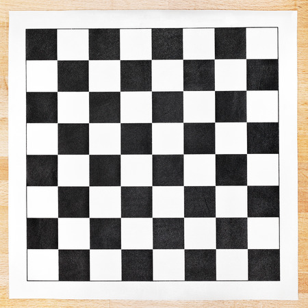 vinyl chessboard with black and white checks on wooden table photo