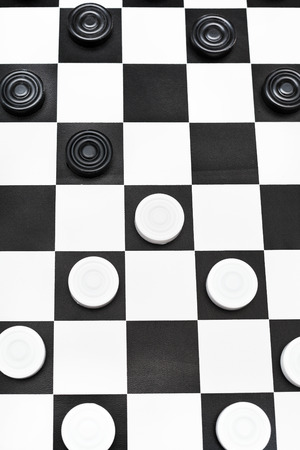 playing position on black and white checked checkers board photo