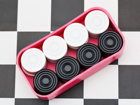 draughts: box with draughts on black and white checkerboard