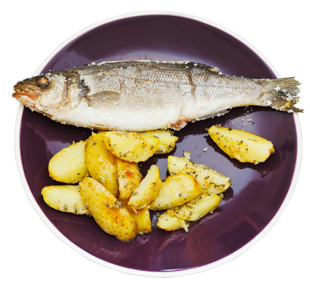 seabass: top view of seabass fish baked in salt and fried potatoes on ceramic plate isolated on white