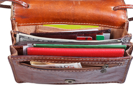 pochette: money, credit cards, pasport in small open ladies handbag isolated on white