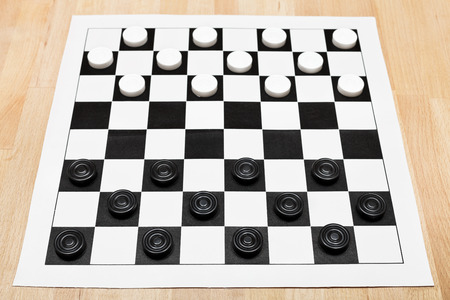 draughts: Starting position on vinyl 8x8 draughts board on wooden table