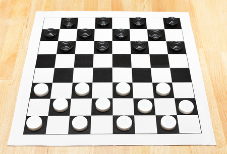Starting position on vinyl 8x8 checkers board on wooden table photo