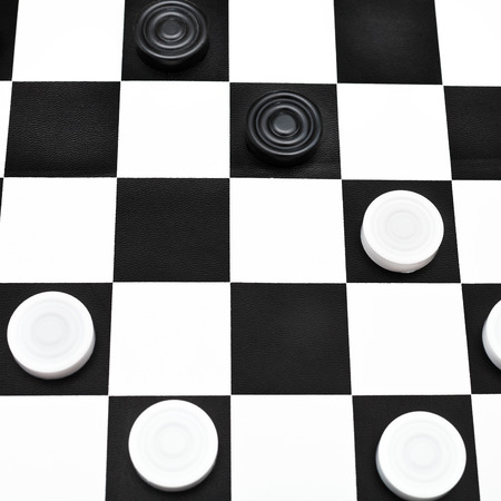 playing position on black and white checked draughts board photo