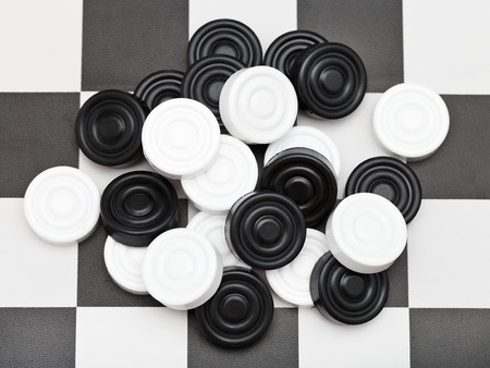 draughts: pile of draughts on black and white checkerboard