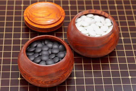 bowl game: black and white go game stones in wooden bowl Stock Photo