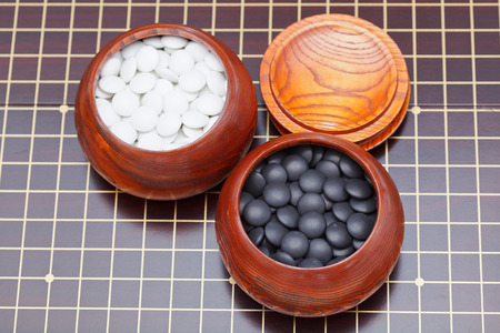 bowl game: above view of black and white go game stones in wooden bowl