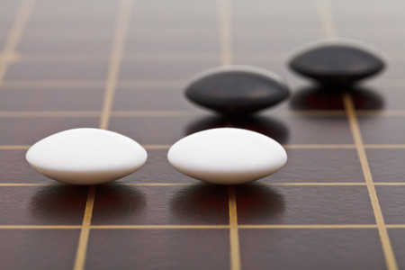 position of few stones during go game playing on wooden board close up