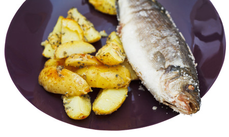 seabass: pescado de lubina al horno en sal y patatas fritas en un plato de cer�mica aislado en blanco Foto de archivo