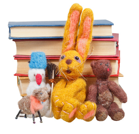 felt soft toys near stack of books isolated on white  photo