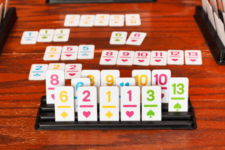 rummy: set of tiles in rack during playing in rummy game on wooden table Stock Photo