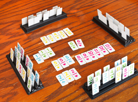 rummy: playing field of rummy card game on wooden table Stock Photo