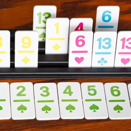 rummy: card rack close up - playing in rummy card game on wooden board