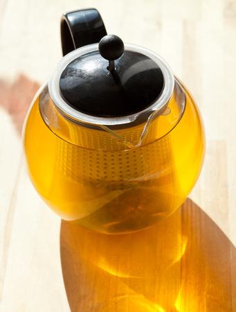 green tee in glass teapot lit by sun light photo