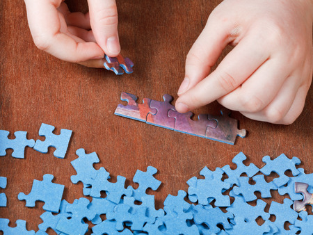 fitting of jigsaw puzzles on wooden table photo